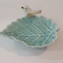 קערית חרסינה מעוצבת בצורת עלה מעוטרת בציפור